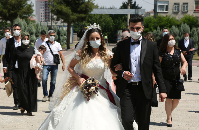 A bride and groom walk to their wedding in face masks amid the coronavirus pandemic (photo credit: REUTERS/SERTAC KAYAR)