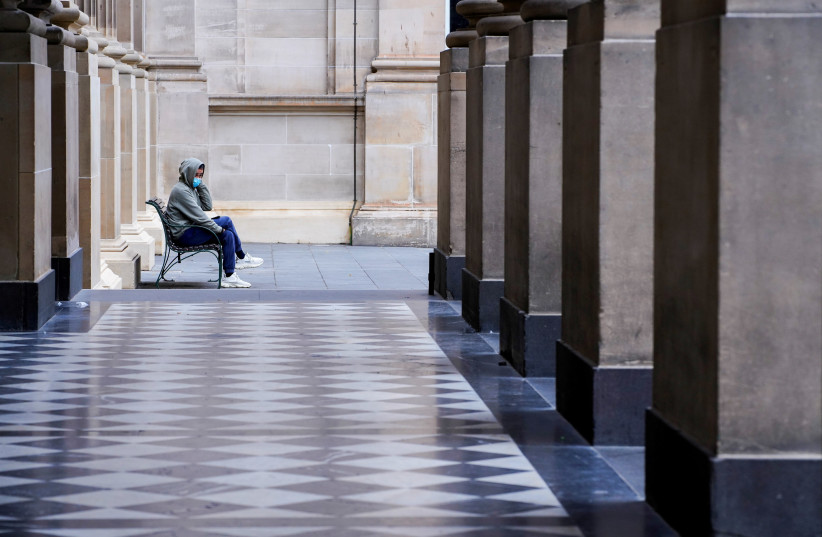 A lone man wearing a protective face mask sits at an unusually quiet State Library on the first day of a lockdown as the state of Victoria looks to curb the spread of a coronavirus disease (COVID-19) outbreak in Melbourne, Australia, July 16, 2021. (credit: REUTERS/SANDRA SANDERS/FILE PHOTO)