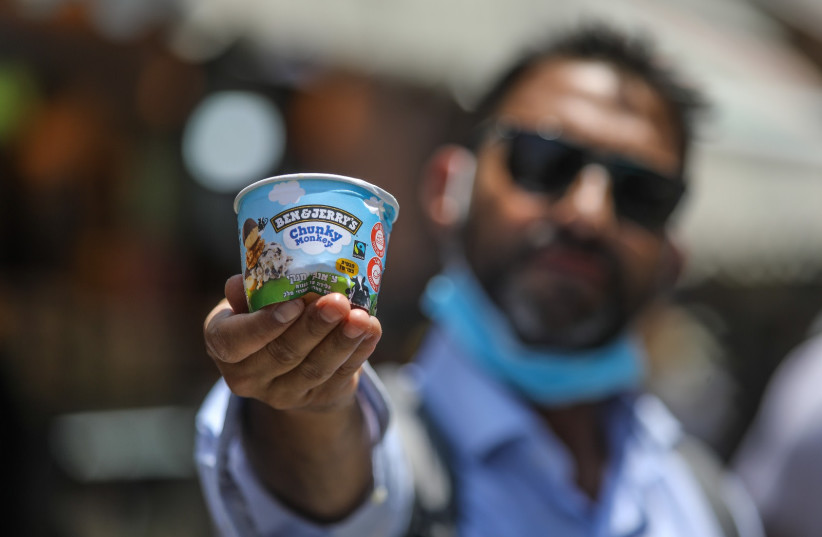 A man holds a small cup of Ben & Jerry's ice cream, Jerusalem (photo credit: MARC ISRAEL SELLEM)