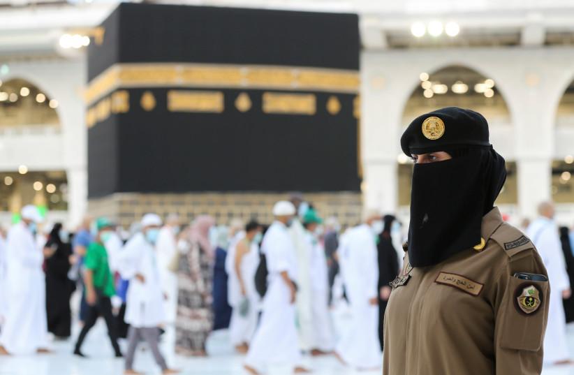 A female Saudi police officer stands guard as pilgrims perform Tawaf during Hajj/Mecca, Saudi Arabia. (photo credit: REUTERS/AHMED YOSRI)