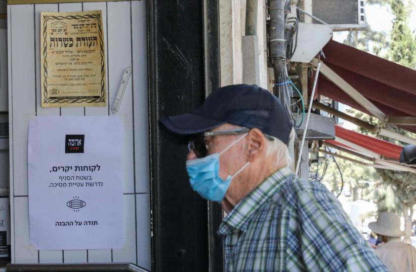 Man walks into Aroma wearing a mask (photo credit: MARC ISRAEL SELLEM)