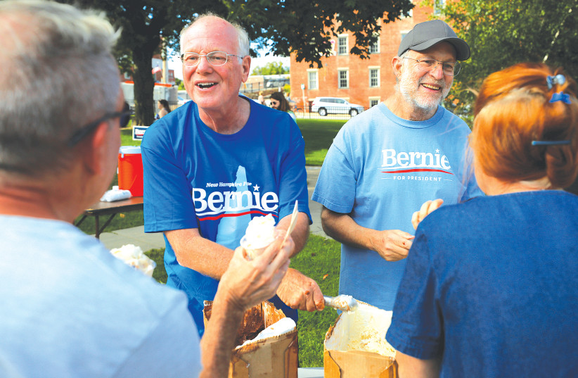 COMPANY FOUNDERS Ben Cohen and Jerry Greenfield serve their Ben and Jerry's ice cream before a campaign rally in Dover, New Hampshire.  (photo credit: BRIAN SNYDER/REUTERS)