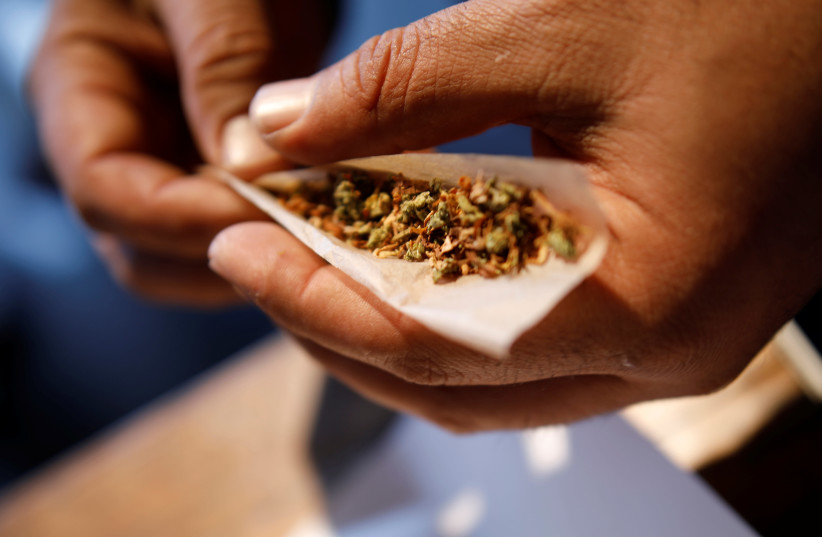 A man prepares a cigarette mixed with marijuana during Cannatech 2017, an annual global cannabis industry event, in Tel Aviv, Israel March 20, 2017. (photo credit: REUTERS/AMIR COHEN)