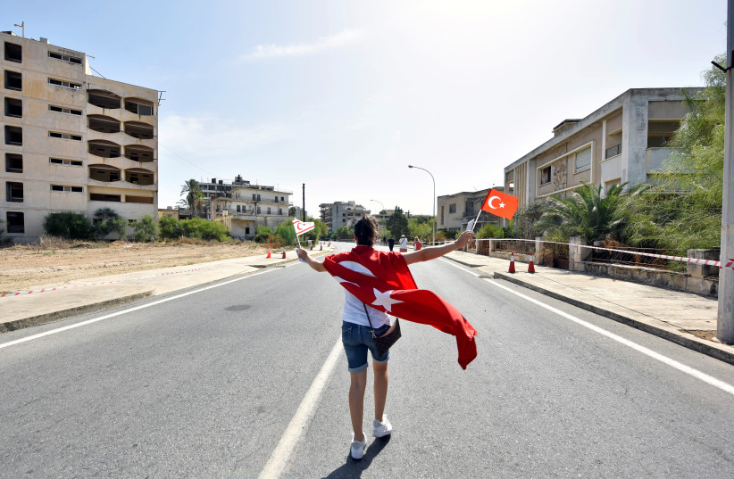 A woman walks while holding Turkish and Turkish Cypriot flags inside an area fenced off by the Turkish military since 1974, in the abandoned coastal area of Varosha, a suburb of the town of Famagusta in Turkish-controlled northern Cyprus, October 8, 2020. (photo credit: REUTERS/HARUN UCAR)