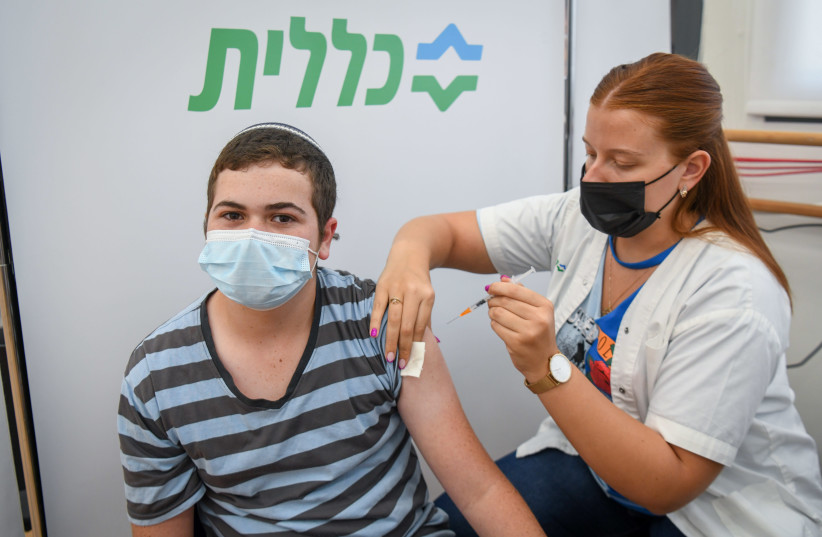 A YOUTH receives the COVID-19 vaccine at a Clalit inoculation center in Petah Tikva last week. (credit: FLASH90)