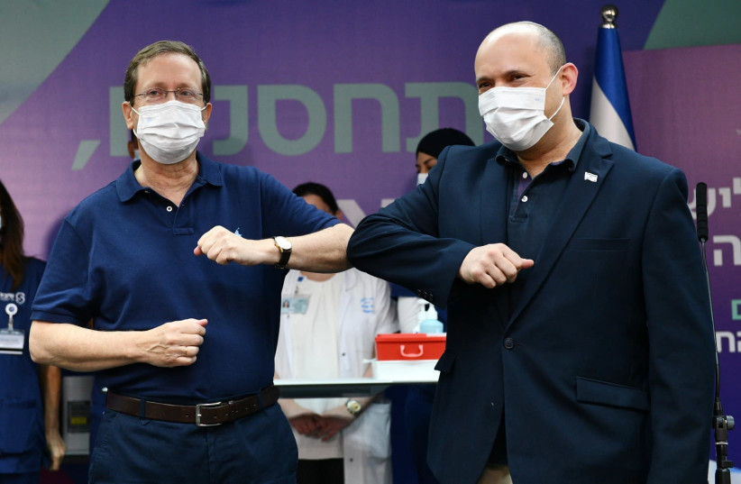 President Isaac Herzog and Prime Minister Naftali Bennett are seen kicking off Israel's third booster shot vaccinations at Sheba Medical Center, on July 30, 2021. (credit: HAIM ZACH/GPO)