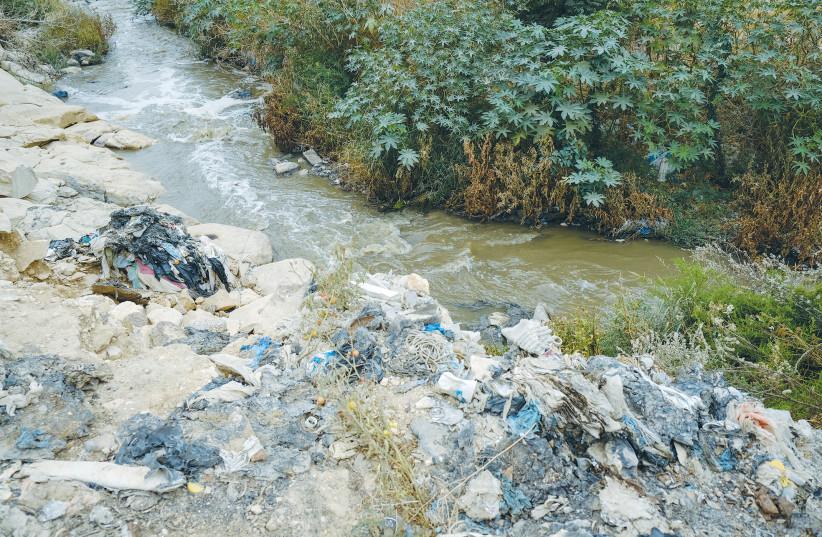 GARBAGE COVERS the banks of a stream in the Judean desert in 2019. (credit: SARA KLATT/FLASH90)