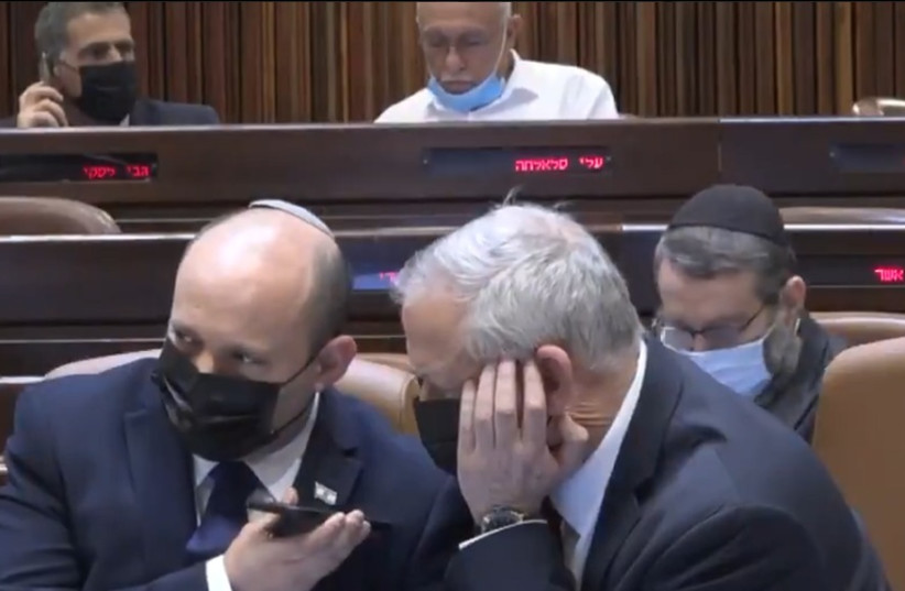 Prime Minister Naftali Bennett and Defense Minister Benny Gantz were updated about rocket fire from Lebanon while in the Knesset plenum.August 4, 2021. (photographer: SCREENSHOT/KNESSET CHANNEL)