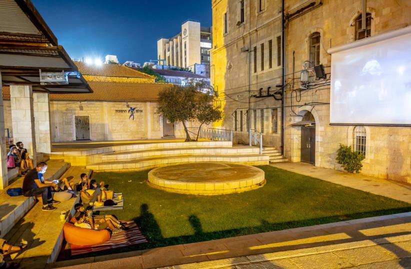 Jerusalem residents watch a film in Kikar HaYareach as part of the Moonlight Cinema project organised by the Jerusalem Municipality   (photo credit: HODAYA TOLEDANO)