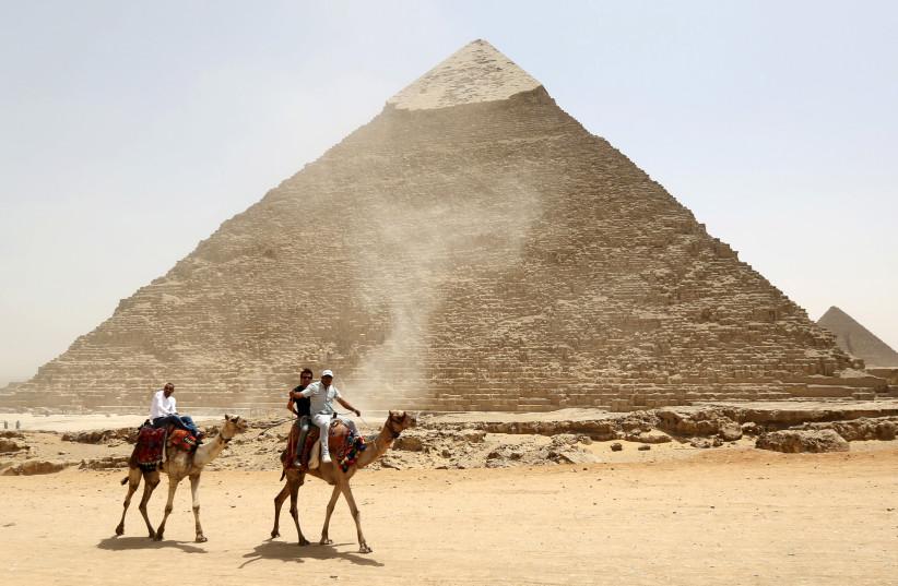 سائحون يمتطون الجمال بجوار هرم خوفو على أهرامات الجيزة العظيمة ، في ضواحي القاهرة (تصوير: رويترز / محمد عبد الغني)