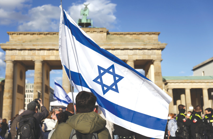 A man waves an Israeli flag during a rally against antisemitism, in front of the Brandenburg Gate in Berlin in May.  (credit: CHRISTIAN MANG / REUTERS)