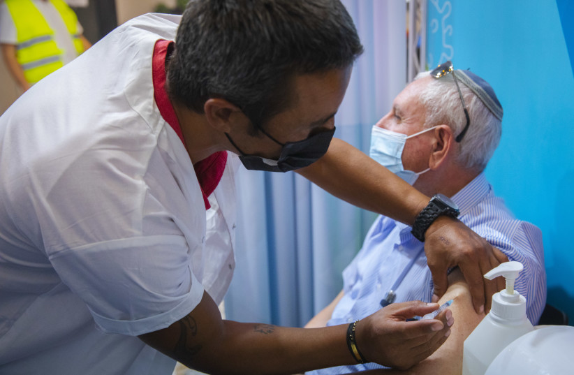 Israelis above 60 years old receive their third dose of the COVID-19 vaccine at a Clalit health care maintenance organization, on August 08, 2021  in Jerusalem.   (photo credit: OLIVIER FITOUSSI/FLASH90)