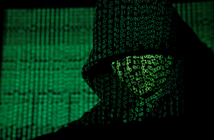 Projection of cyber code on hooded man (llustrative) (credit: REUTERS/KACPER PEMPEL/ILLUSTRATION TPX IMAGES OF THE DAY)