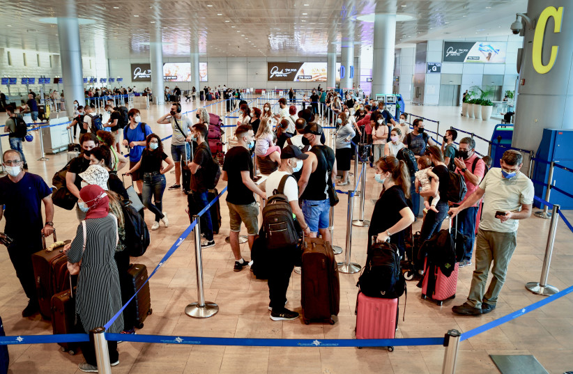 Travellers wear protective face masks at Terminal 3, Ben Gurion International Airport, as Israel restricts air travel more, on August 05, 2021.  (credit: AVSHALOM SASSONI/FLASH90)