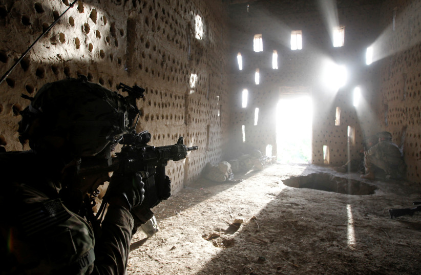Le soldat américain Nicholas Dickhut, du 5-20 Infantry Regiment, attaché à la 82nd Airborne, pointe son fusil vers une porte après avoir essuyé des tirs des talibans alors qu'il patrouillait dans le district de Zharay dans la province de Kandahar, Afghanistan, le 26 avril 2012. (Crédit photo: BAZ RATNER/REUTERS)