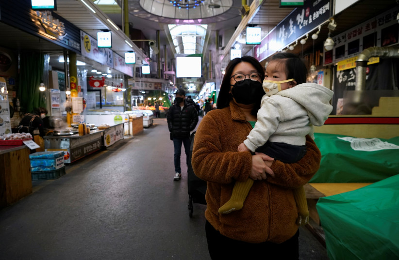A mother and her child wearing masks to prevent contacting the coronavirus, shop at a traditional market in Seoul (credit: REUTERS/KIM HONG-JI)
