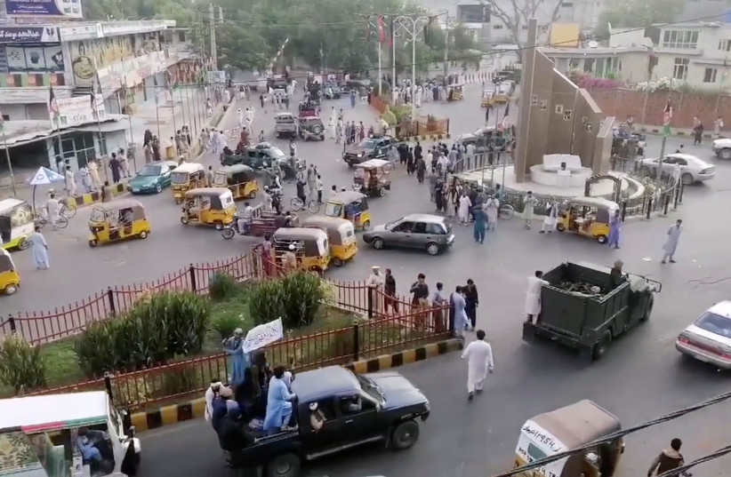 Taliban militants waving a Taliban flag on the back of a pickup truck drive past a crowded street at Pashtunistan Square area in Jalalabad, Afghanistan in this still image taken from social media video uploaded on August 15, 2021. (photo credit: SOCIAL MEDIA WEBSITE/VIA REUTERS)