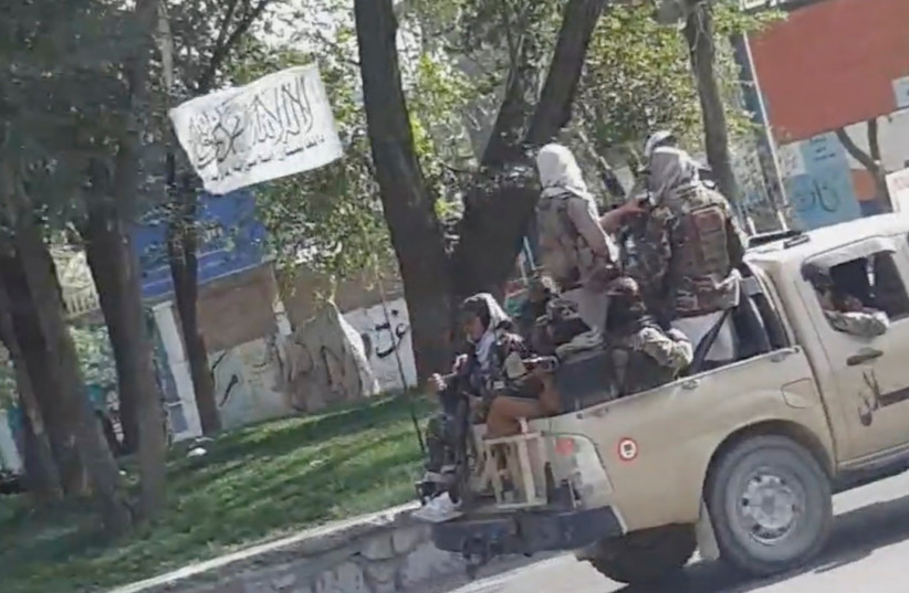 Taliban waving a flag drive through the streets of Kabul, Afghanistan August 16, 2021 in this still image taken from social media video. (credit: SNAPCHAT/ @ mr_khaludi /VIA REUTERS)