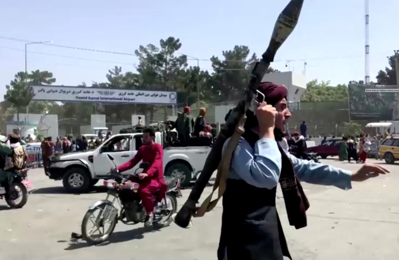 A Taliban fighter runs towards crowd outside Kabul airport, Kabul, Afghanistan August 16, 2021, in this still image taken from a video. (credit: REUTERS TV/via REUTERS)