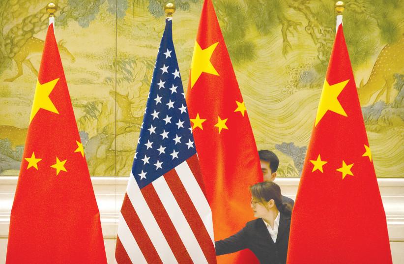 Funcionários chineses ajustam as bandeiras dos EUA e da China antes da sessão de abertura das negociações comerciais sino-americanas em Pequim em fevereiro de 2019. (Crédito da foto: REUTERS / MARK SCHIEFELBEIN / POOL)