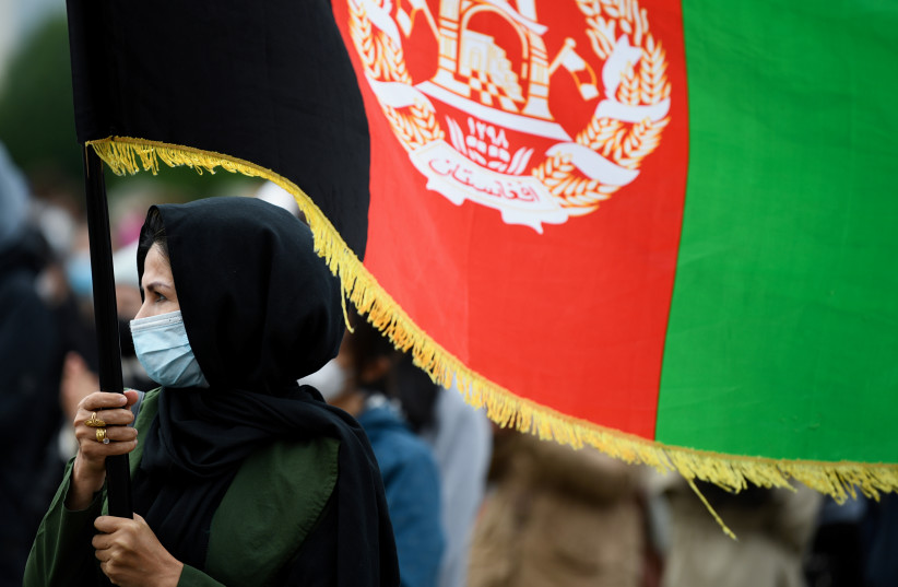 A person holds an Afghanistan's flag during a protest against support for the Taliban, in Berlin, Germany, August 17, 2021 (credit: ANNEGRET HILSE / REUTERS)