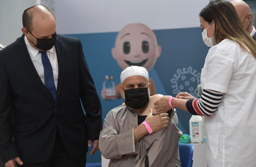 Imam Jawad Masarwa of Taibe receives his third coronavirus vaccine as Prime Minister Naftali Bennett looks on, August 19, 2021. (credit: KOBI GIDON / GPO)