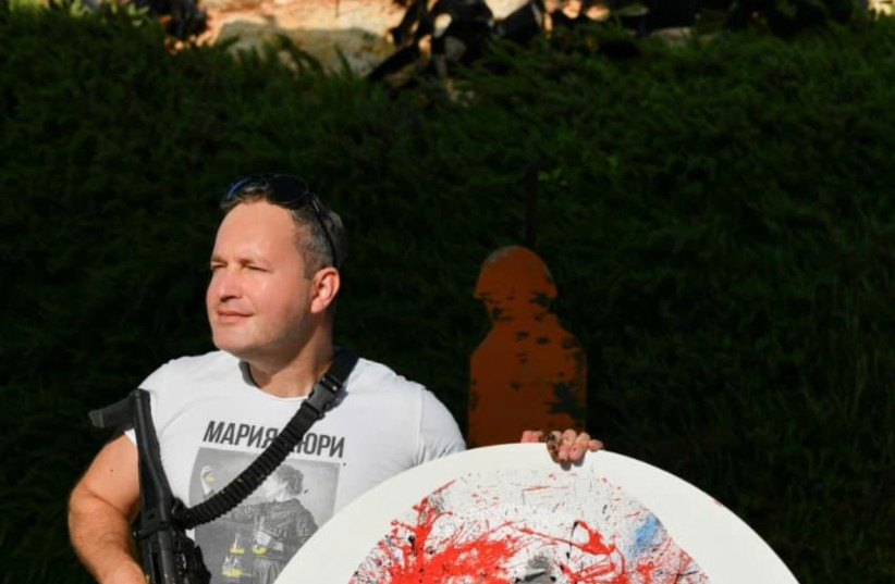 David Roytman is seen with a gun and a piece of abstract art. (credit: Courtesy)