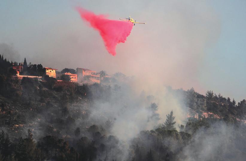 A FIREFIGHTING PLANE disperses fire retardant near Beit Meir, on the outskirts of Jerusalem, on Monday. (credit: AMMAR AWAD/REUTERS)