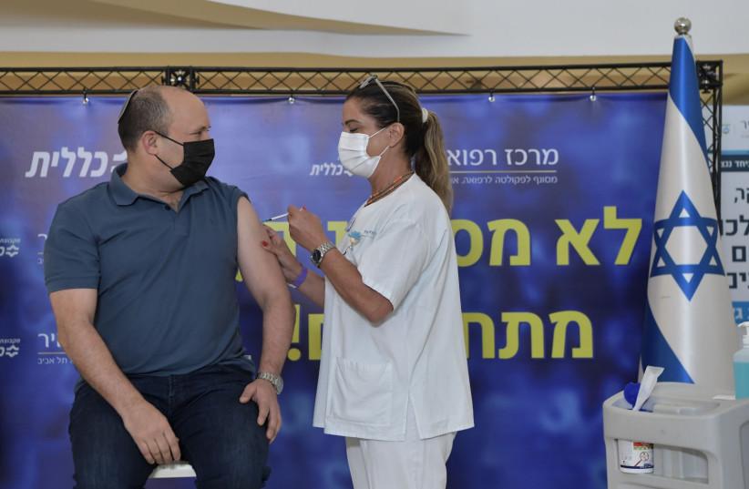 Se ve al primer ministro de Israel, Naftali Bennett, recibiendo su tercera vacuna COVID-19, el 20 de agosto de 2021 (crédito: KOBI GIDEON / GPO).