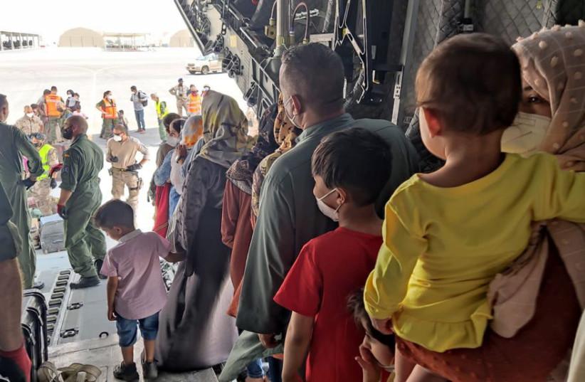 Evacuees from Afghanistan disembark a Spanish military plane as part of their evacuation at Al Maktoum International Airport (DWC) in Dubai, United Arab Emirates, August 20, 2021. (credit: REUTERS)