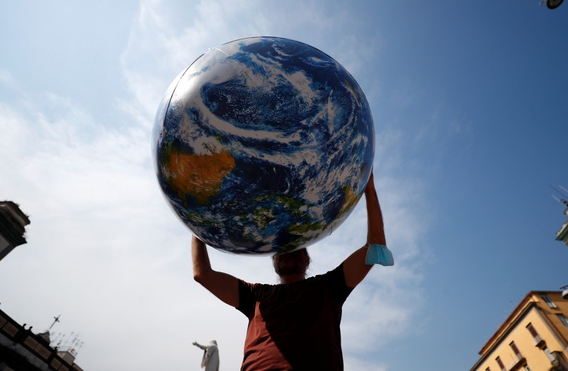 A person holds inflatable Earth as climate activists including Extinction Rebellion and Fridays for Future stage a protest demanding more action whilst G20 climate and environment ministers hold a meeting in Naples, Italy, July 22, 2021. (credit: GUGLIELMO MANGIAPANE / REUTERS)
