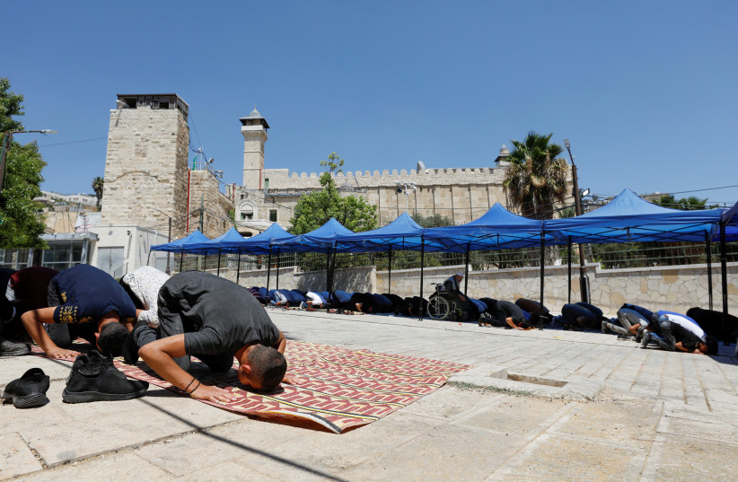 Palestinians attend Friday prayers in Hebron near the Tomb of the Patriarchs, August 20, 2021  (photo credit: REUTERS/MUSSA QAWASMA)