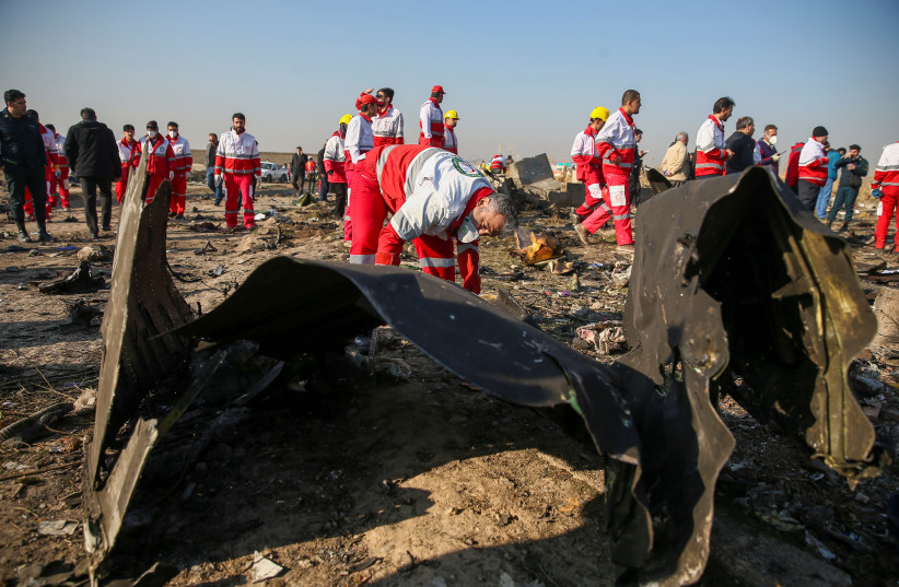 Red Crescent workers check the debris from the Ukraine International Airlines plane, that crashed after take-off from Iran's Imam Khomeini airport, on the outskirts of Tehran (credit: NAZANIN TABATABAEE/WANA VIA REUTERS)