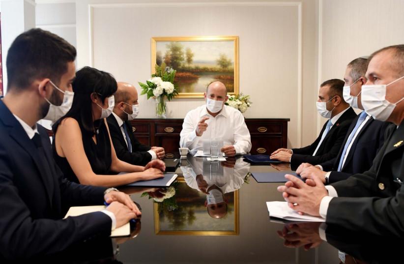 Le Premier ministre Naftali Bennett rencontre ses collaborateurs avant sa rencontre avec le président américain Joe Biden, le 26 août 2021. (Crédit : AVI OHAYON - GPO)