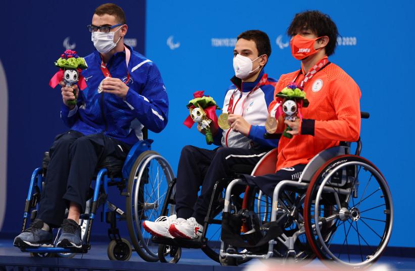 ロシアのパラリンピック委員会の金メダリストのみズベズダノフが銀メダリスト、イスラエルのアミオマールダダたと日本の鈴木孝之と並んで表彰台に歓呼している(出典:REUTERS / MARKO DJURICA)