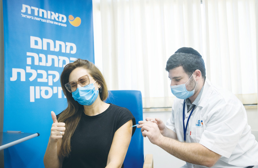 A WOMAN receives a third dose of the COVID-19 vaccine, at Meuhedet vaccination center in Jerusalem, last week.  (credit: YONATAN SINDEL/FLASH90)