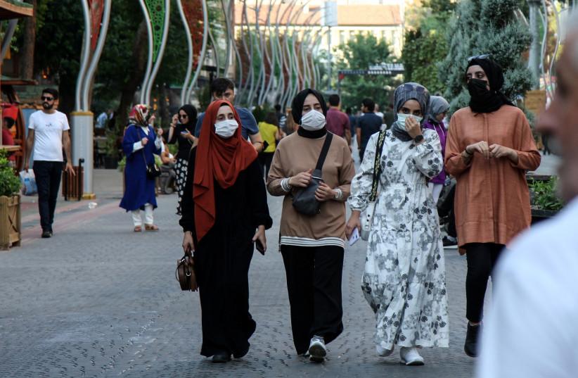 People wearing protective masks walk along a street amid a surge in COVID-19 cases in Diyarbakir, Turkey (credit: SERTAC KAYAR / REUTERS)