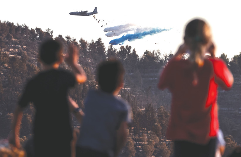 CHILDREN WATCH a military plane disperse fire retardant to extinguish a blaze near Kibbutz Tzuba, outside Jerusalem, last month.  (photo credit: RONEN ZVULUN/REUTERS)