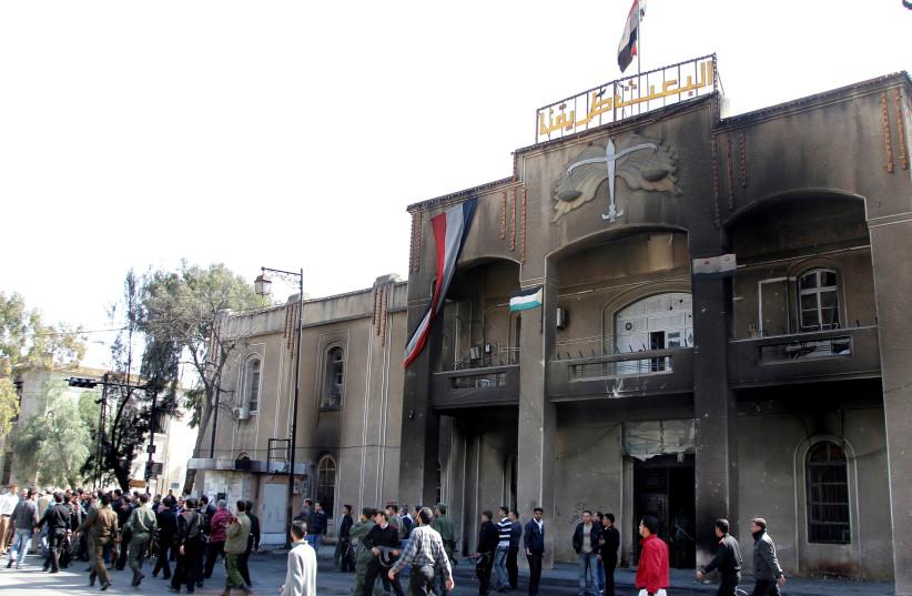 Des gens passent devant le palais de justice principal, qui avait été incendié par des manifestants lors de manifestations réclamant la liberté et la fin de la corruption, à Deraa, le 21 mars 2011. (Crédit: REUTERS/KHALED AL-HARIRI)