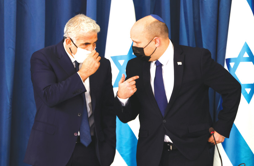 Prime Minister Naftali Bennett chats with Foreign Minister Yair Lapid at the weekly cabinet meeting, August 2021 (credit: RONEN ZVULUN/REUTERS)