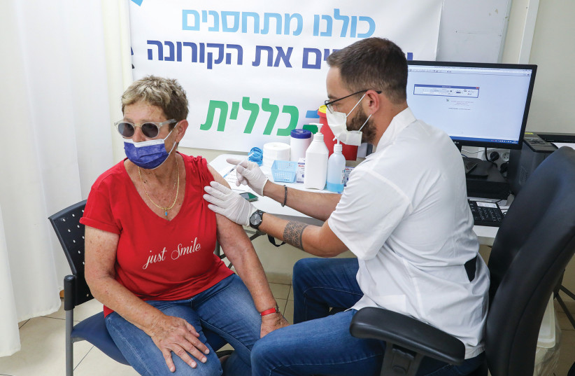 A WOMAN RECEIVES her third anti-COVID vaccination at a Clalit Health Fund center in Jerusalem.  (credit: MARC ISRAEL SELLEM/THE JERUSALEM POST)