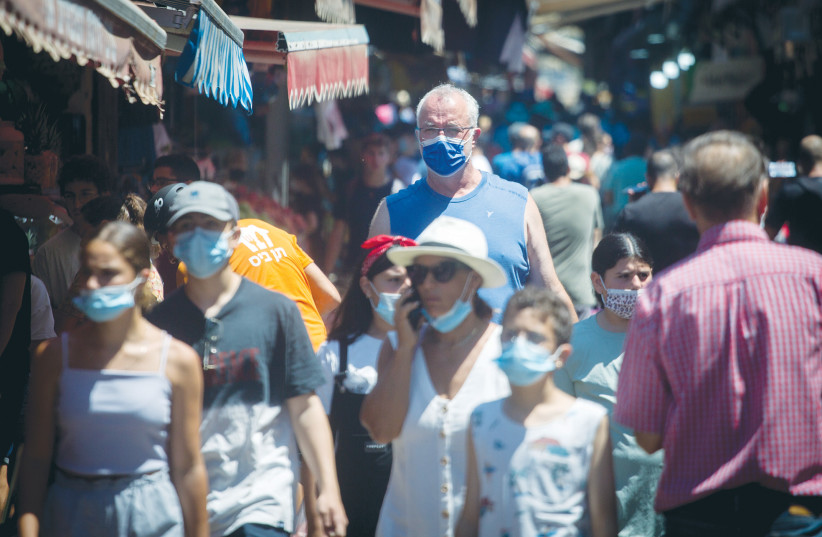 PEDESTRIANS WEAR protective face masks as they walk through the Carmel market in Tel Aviv, last month.  (credit: MIRIAM ALSTER/FLASH90)