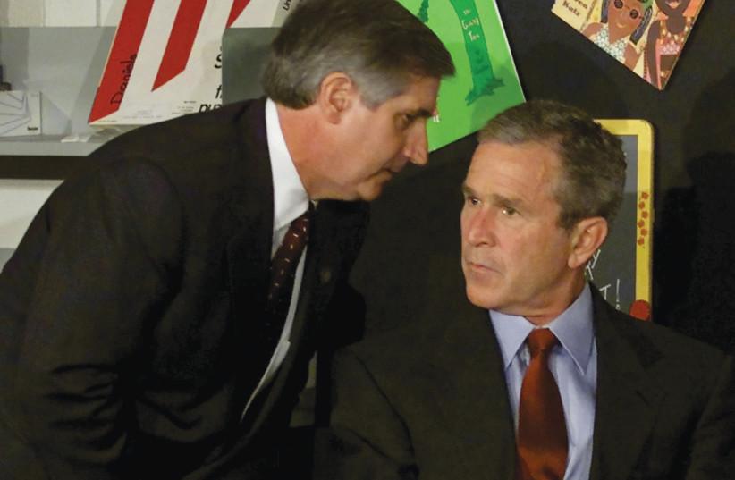 Le président américain George W. Bush est informé qu'un deuxième avion frappe le World Trade Center par le chef d'état-major de la Maison Blanche, Andrew Card, dans une école primaire de Sarasota, en Floride, le 11 septembre 2001. (Crédit : WIN MCNAMEE/REUTERS)