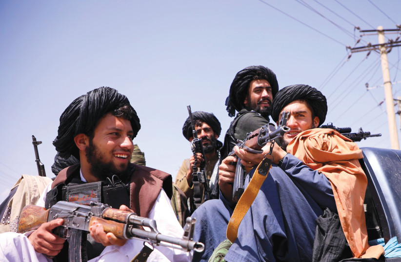 TALIBAN FORCES patrol in front of  Hamid Karzai International Airport  in Kabul, Afghanistan, September 2 (photo credit: STRINGER/ REUTERS)