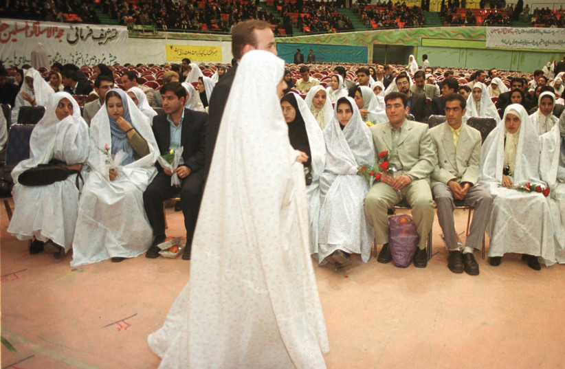 A just-married Iranian couple walks past other couples attending a mass wedding celebration at Azadi Sport Centre in Tehran February 27, 2002 where about 900 people tied the knot. (photo credit: REUTERS/Nikoubazl CJF/GB)
