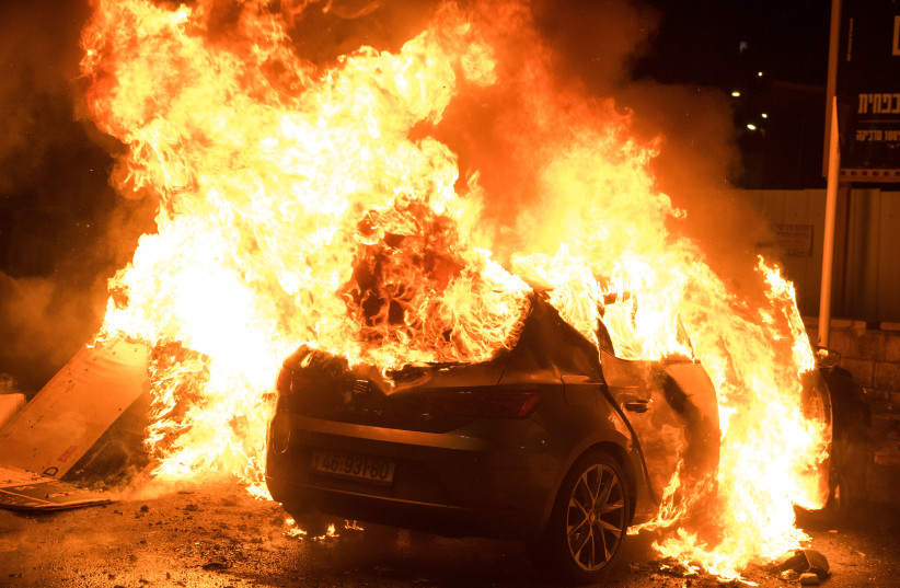 A CAR is set aflame during clashes between Arabs and Jews in Acre, May 12.  (credit: RONI OFER/FLASH90)