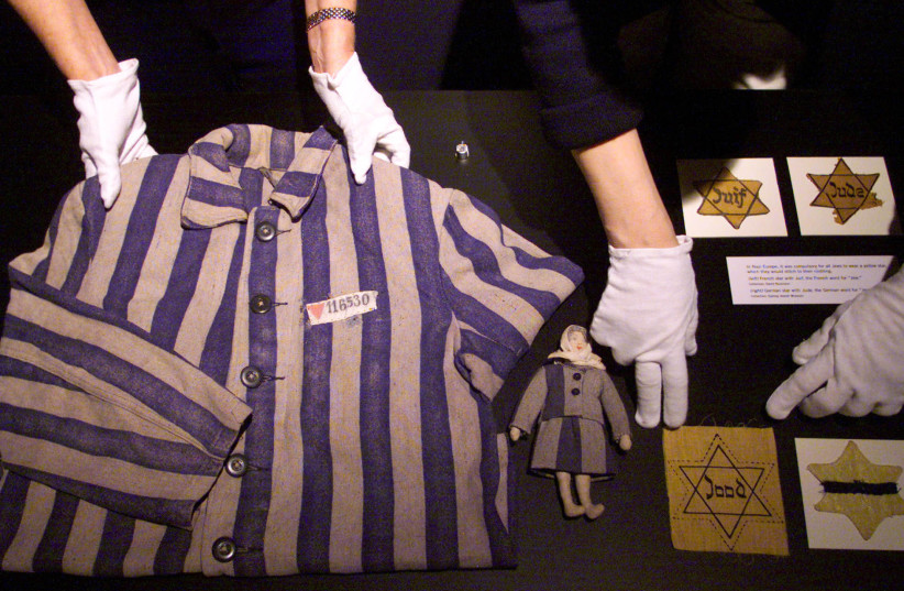 CURATORS LAY out a concentration camp uniform from 1944 Bergen-Belsen, a child's doll and Jewish stars at the Powerhouse Museum in Sydney, Australia. (photo credit: REUTERS)