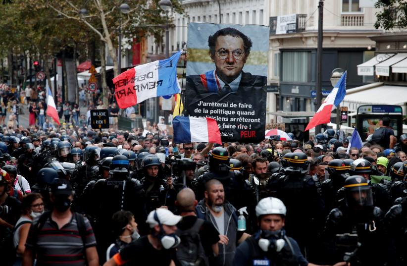 Des manifestants brandissent une banderole avec une image de feu l'humoriste français Coluche lors d'une manifestation contre les restrictions imposées par la France, y compris les laissez-passer de santé obligatoires, pour lutter contre la pandémie de la maladie à coronavirus (COVID-19), à Paris, France, le 11 septembre 2021. (Crédit photo : REUTERS)