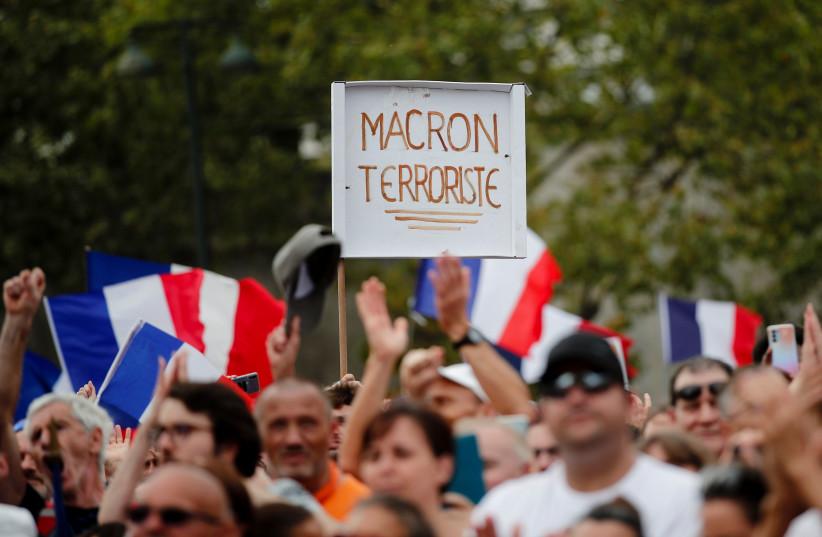 Un manifestant tient une pancarte indiquant '' Macron terroriste'' lors d'une manifestation appelée par le parti nationaliste français '' Les Patriotes '' (Les Patriotes) contre les restrictions imposées par la France pour lutter contre l'épidémie de maladie à coronavirus (COVID-19), le ' Esplanade des