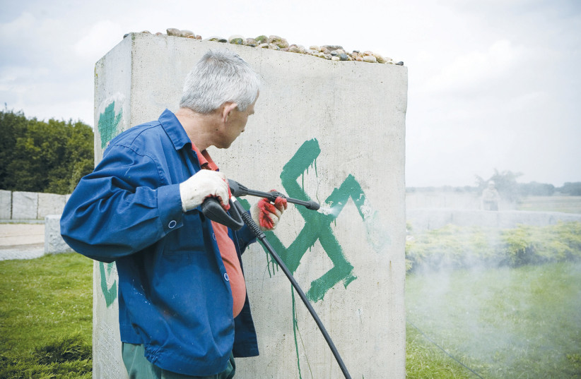 A PRESSURE hose is used to clean a monument with Nazi swastikas painted over it in Jedwabne, Poland, in this 2011 illustrative photo (photo credit: Jendrzej Wojnar/Agencja Gazeta/Reuters)